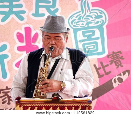 Playing The Saxophone At An Outdoor Festival