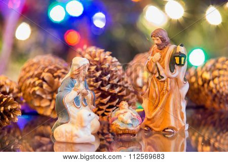 Nativity Set With Mary, Joseph And Jesus With Christmas Lights Background