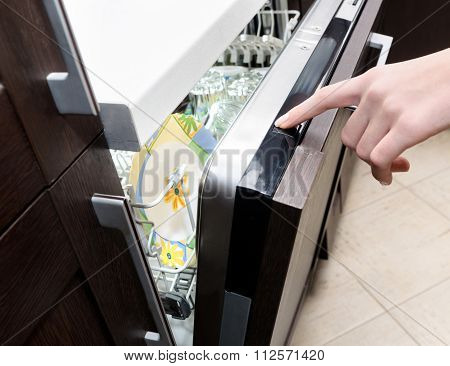 Female hand presses the start button on the dishwasher.