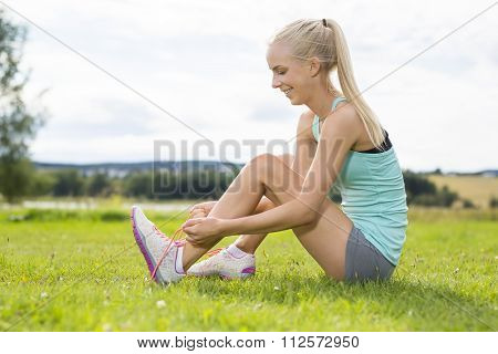 Smiling female runner tying shoe laces at the grass