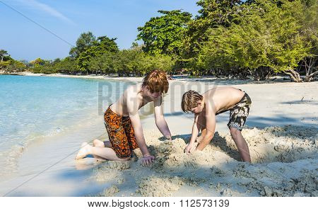 Boys Enjoy Playing At The Sandy  Beach