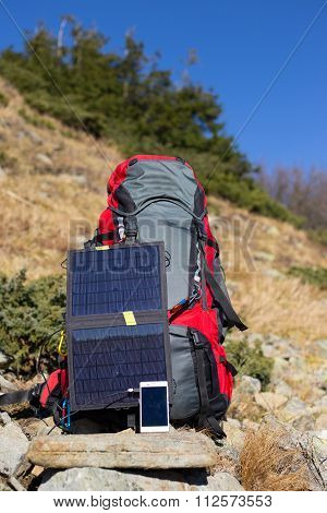 The solar panel attached to the tent. The man sitting next to mobile phone charges from the sun.