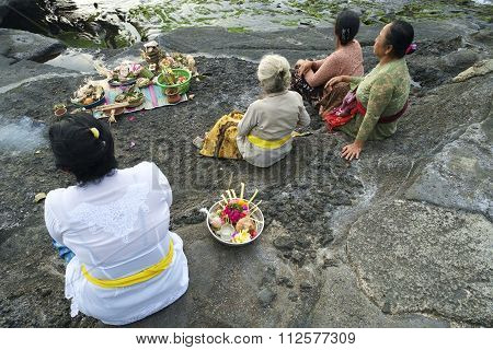 Balinese Hindu devotees pray at sunset on the rocky beaches.