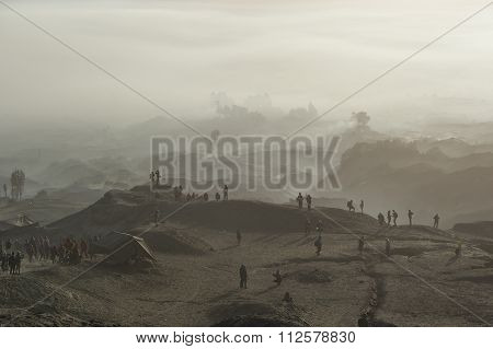 Tourist trekking along Mount Bromo misty ridge
