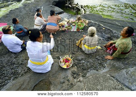 Balinese Hindu devotees pray at sunset on the rocky beaches