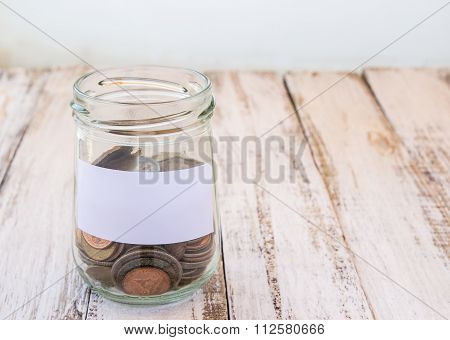 Money In The Glass On Wooden Table