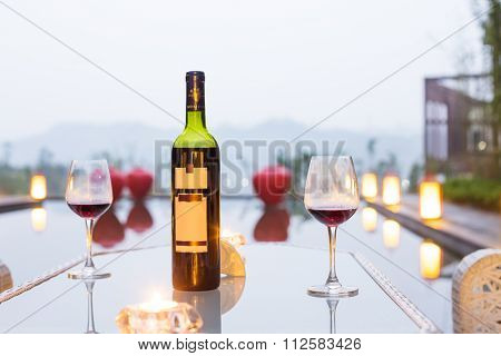 red wine and glass on table outdoors in gloomy sky