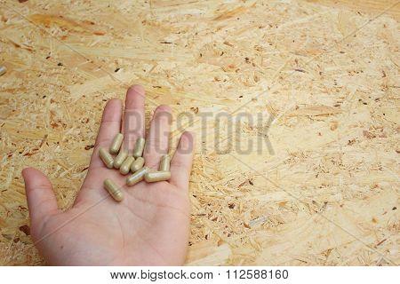 Medicine Pills In Hand On Wooden Background.