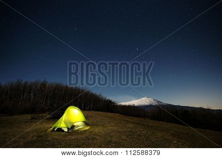 lighting tent and Etna Volcano under moonlight and starry sky , Nebrodi Park in Sicily