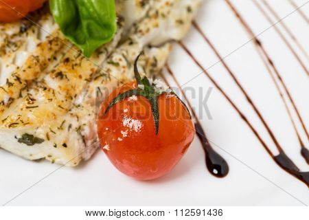 Baked fish fillet with tomatoes.