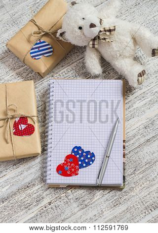 Open  Clean Notepad,  Homemade Valentine's Day Gifts In Kraft Paper, Paper Hearts, Toy Bear On White