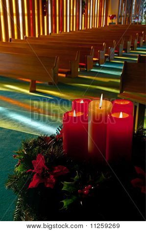 Lit Christmas Candles And Wreath In Empty Church