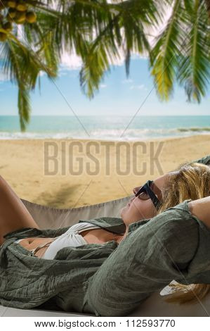 Blond girl lying in hammock on the tropical beach