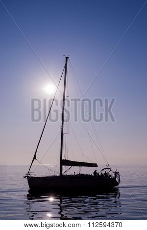Sailing boat yacht on the horizon in the blacklight with the sea and sky