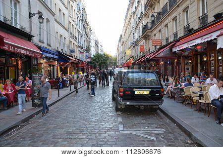 PARIS, FRANCE - SEPTEMBER 9, 2014: Latin Quarter of Paris France. Narrow street of Paris among old traditional parisian houses and cafe in Paris.