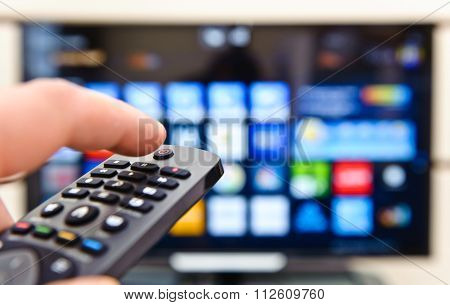 Smart tv and hand pressing remote control.
