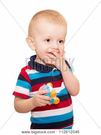 The Little Fair-haired Boy In A Striped T-shirt Covered A Mouth With A Palm And Looks With Astonishm