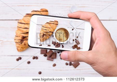 Hands taking photo cup of coffee with croissants with smartphone.