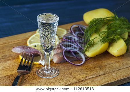 Glass of vodka, herring, red onion and potatoes