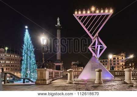 LONDON, UK - DECEMBER 19: Night shot of Menorah next to Christmas tree in Trafalgar Square, set up for Chanukah. December 19, 2015 in London.