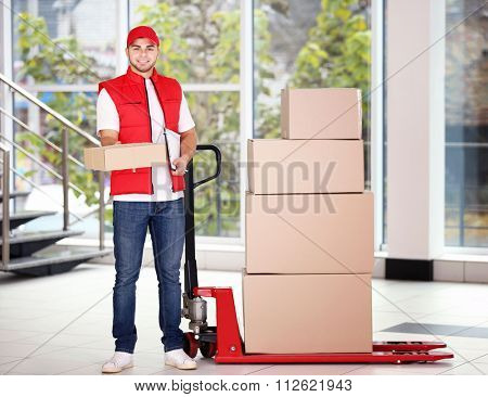 Delivery concept - postman in red uniform with parcels on dolly