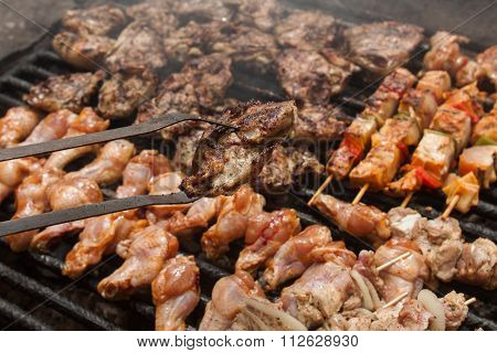 various meat chicken wings steaks grilled on brazier