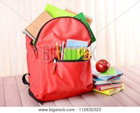 Full of stationary red backpack and pile of books with apple on top on wooden table