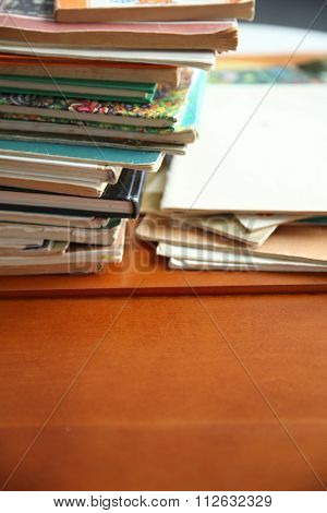 Pile of old books on brown table in the room