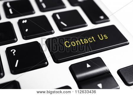 Close-up of laptop keyboard with color button and text Contact Us