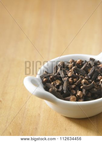 clove in a white container on the wooden background