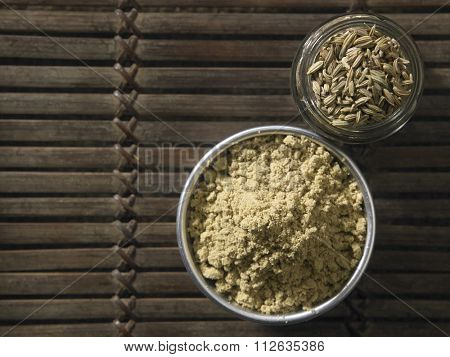 cumin powder and cumin seeds on wooden background