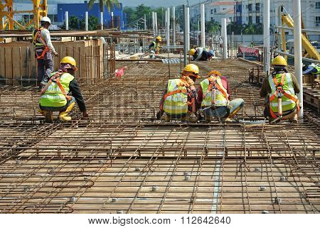 Construction workers fabricating floor slab reinforcement bar
