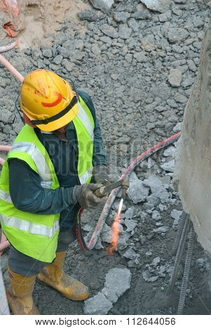 Workers using blowtorch to cut metal at construction site.