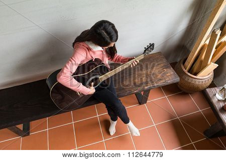 Top view of woman play with guitar