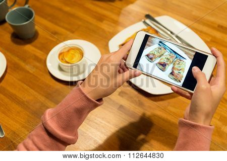 Woman use of the cellphone for taking the picture of the food