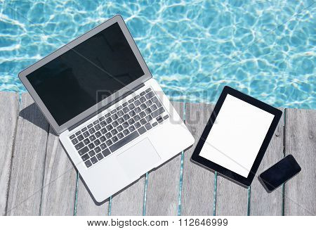 Laptop, tablet computer and mobile phone by the pool