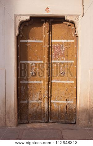 Traditional Brown Wooden Door With Ornate Stone Doorframe In Junagarh Fort, Bikaner, Partially Open