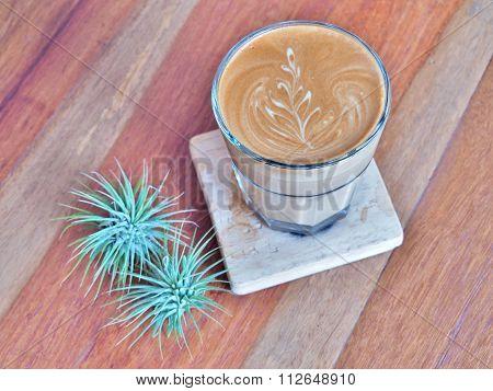 Latte art coffee on the wood saucer.