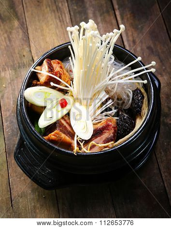 stock pot on a stove with vegetables enokitake and beef