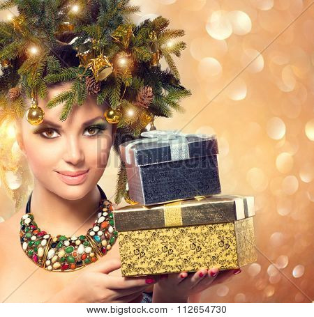 Winter Woman with New Year Gifts. Fairy. Beautiful New Year and Christmas Tree Holiday Hairstyle and Make up. Beauty Fashion Model Girl With Present Box over golden glowing background