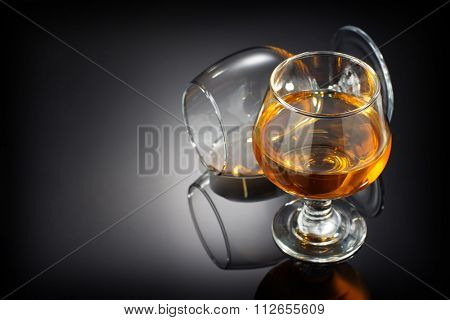 cognac and  glass on black background