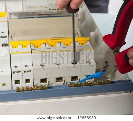 electrical appliance repairs. electrician fixing cable in domestic electrical box