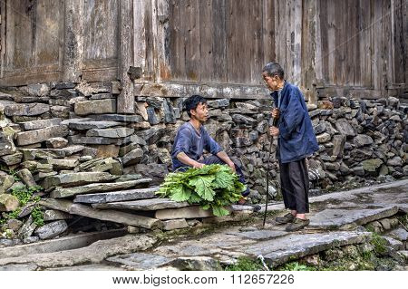 An Old And Younger Farmers Talking Near Wooden Shed.