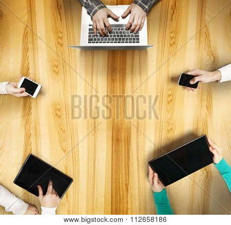 View above desk with peoples hands with gadgets