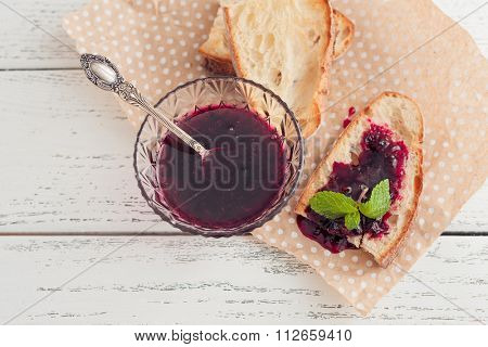 grilled crusty bread with black currant jam on wooden background