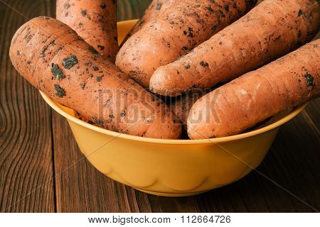 Unpeeled Carrots In Plate On Wooden Table