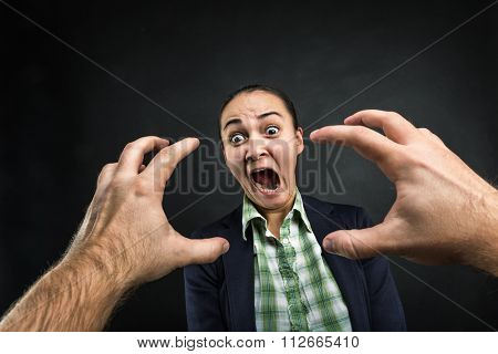 Young woman frightened with huge human hands