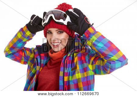 Young smiling woman is posing with ski goggles in studio, isolated on white background.