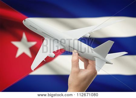 Airplane In Hand With Flag On Background - Cuba