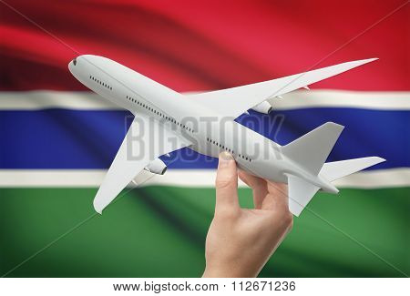 Airplane In Hand With Flag On Background - Gambia